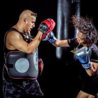 woman hitting boxing pad