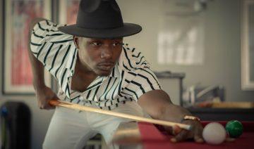 black man playing billiards